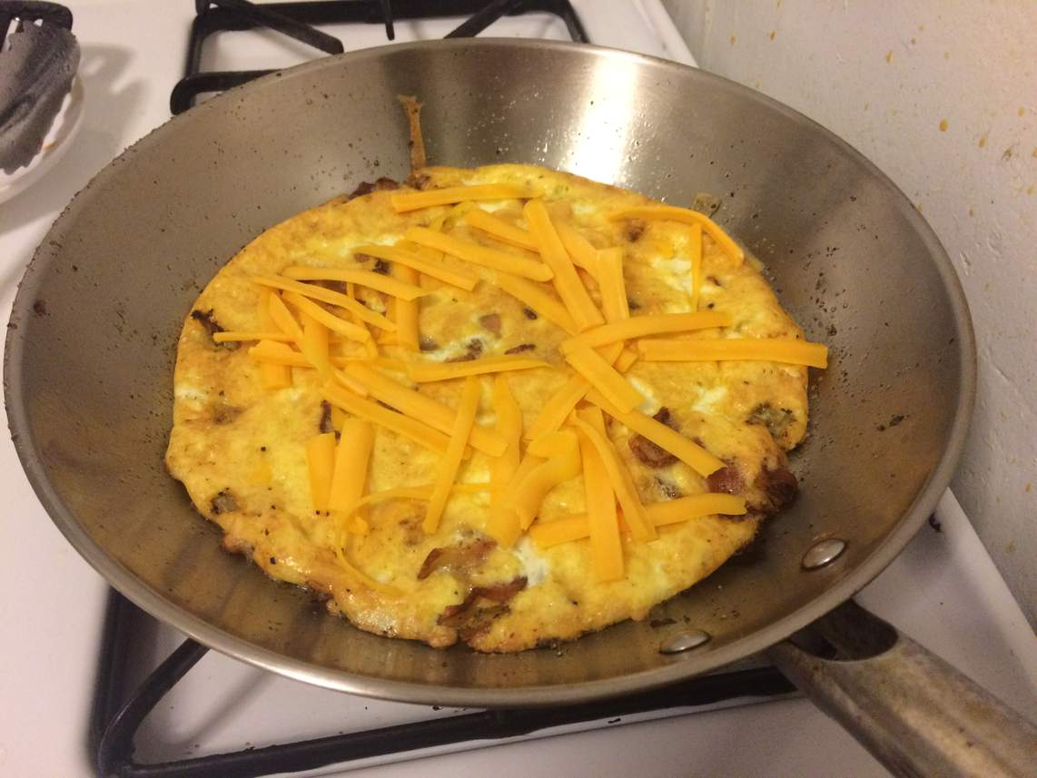 Bacon and onion frittata fresh out of the oven with cheddar cheese on top